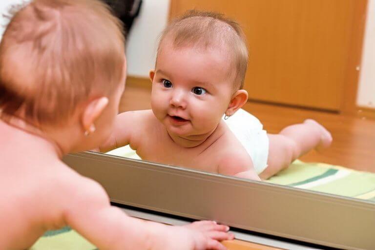 Bebis som tittar förvånat i spegeln.