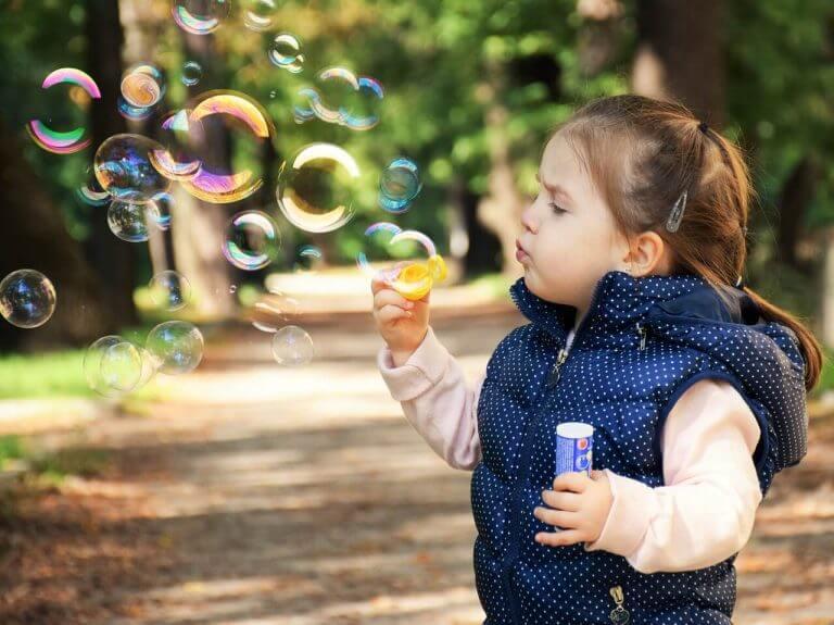 Flicka som blåser bubblor.