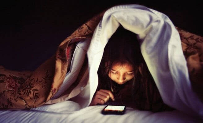 barn med mobiltelefon under täcke