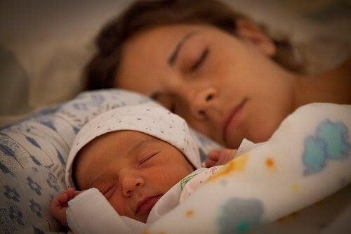 kvinna och spädbarn sover