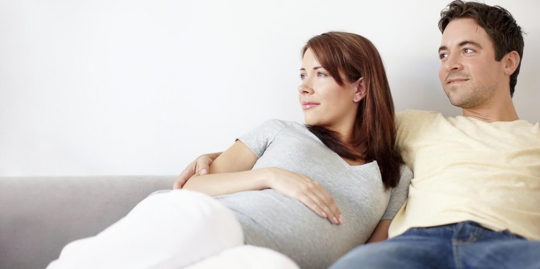 man och gravid kvinna i soffa