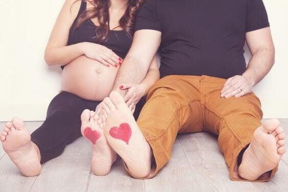 gravid kvinna och man med hjärtan målade på fotsulorna