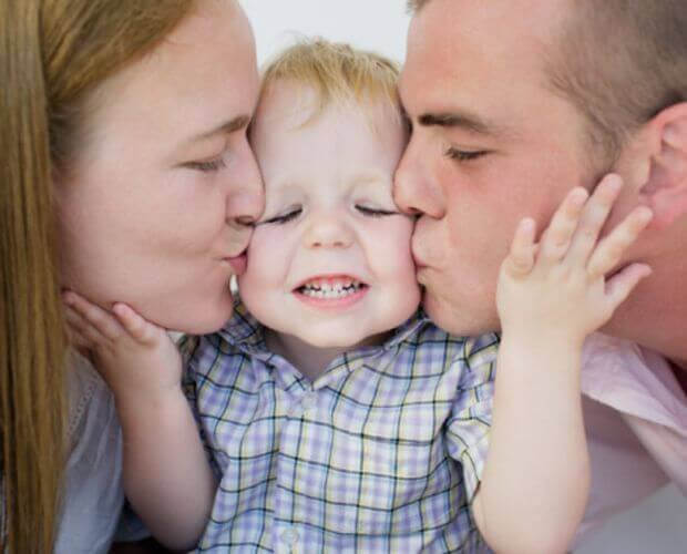 mamma och pappa pussar barn på var sin kind