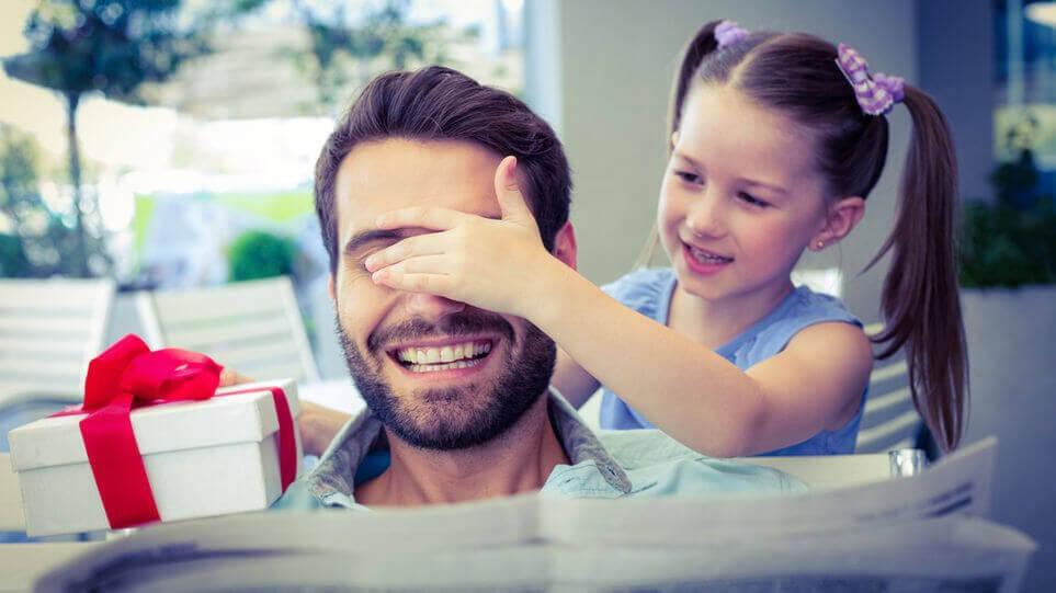 flicka ger pappa present och håller för ögonen på honom