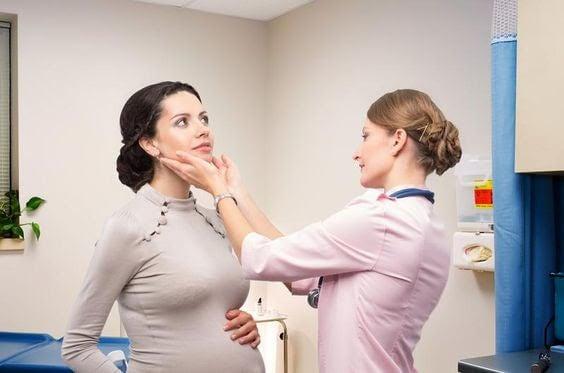 läkare undersöker gravid kvinna