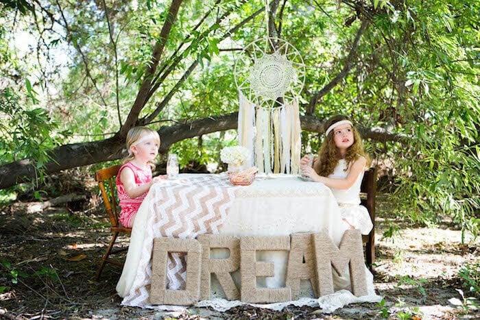 """två flickor sitter vid ett bord med ordet """"DREAM"""" på och en drömfångare hänger ovanför dem"""