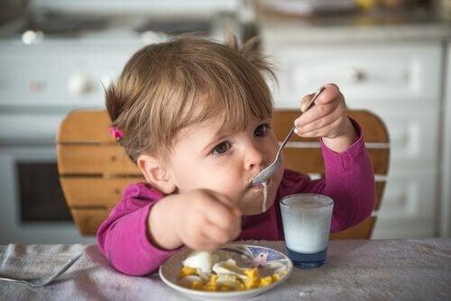 baby äter yoghurt och frukt