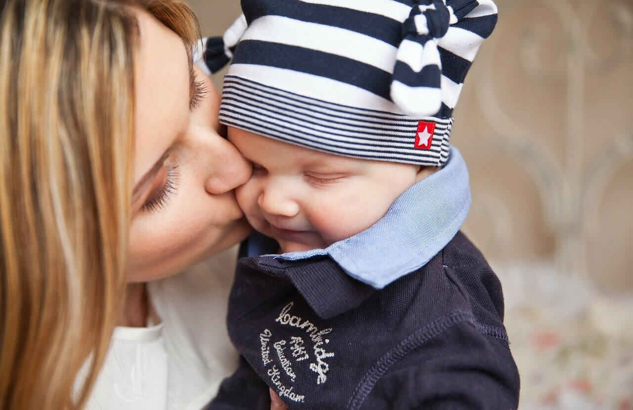 mamma pussar baby med mössa