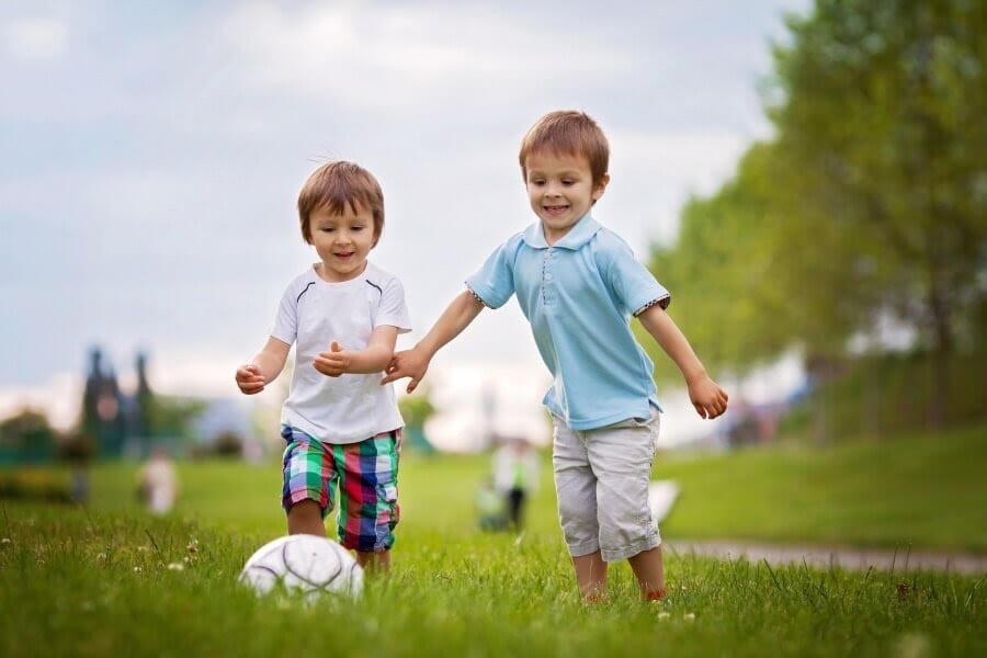 två glada barn med fotboll