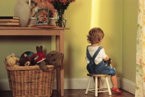 liten flicka sitter i skamvrån
