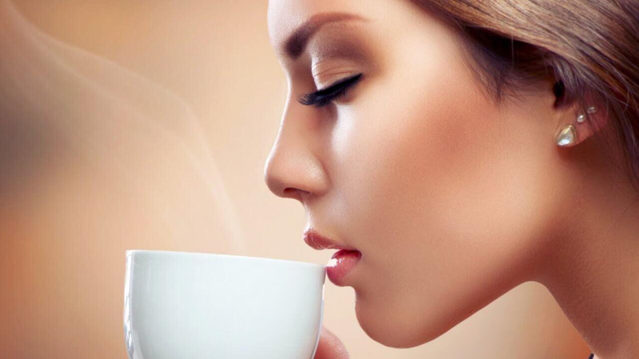 kvinna dricker en kopp kaffe med slutna ögon