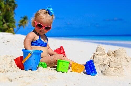 baby på stranden med sandleksaker
