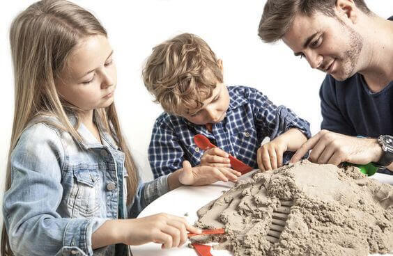 Familj leker med magisk sand
