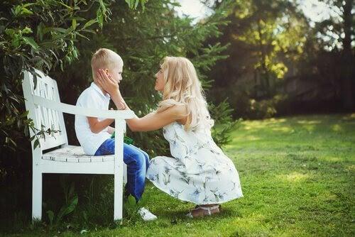 Mamma tröstar son på bänk