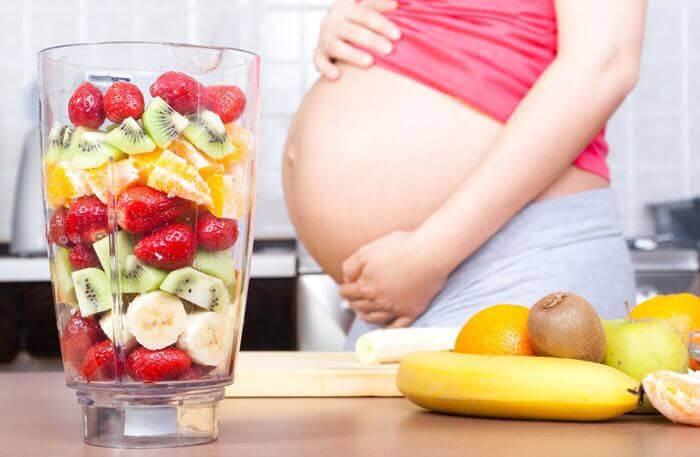 gravid kvinna visar upp magen bredvid en mixer med frukt
