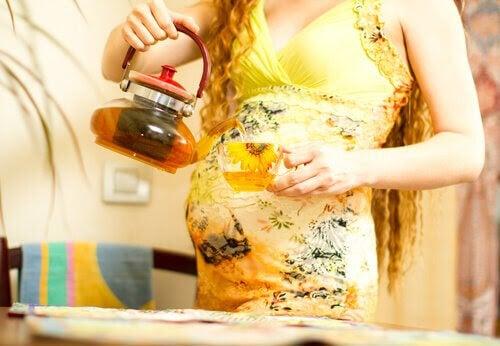 gravid kvinna häller upp te