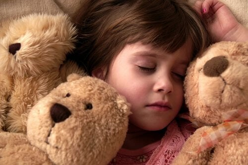 Barn som sover med nalle.