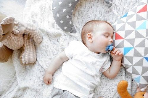 Bebis med napp i sängen.