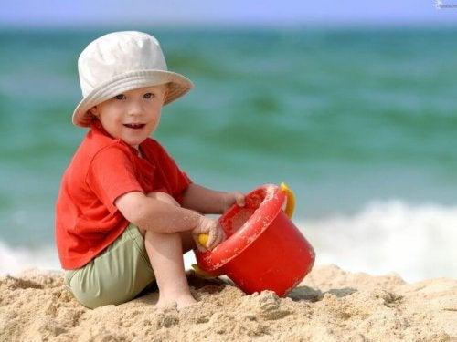 Ett barn leker med hink och spade.