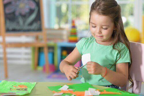 En flicka klipper i papper.
