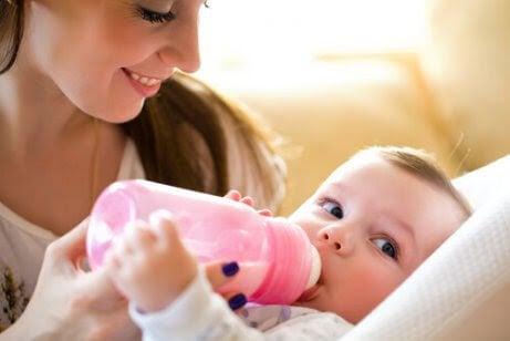 Hål i tänderna av nappflaskan: baby med nappflaska