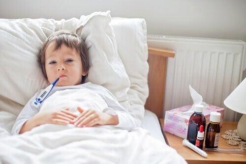sjukt barn i säng med febertermometer i munnen