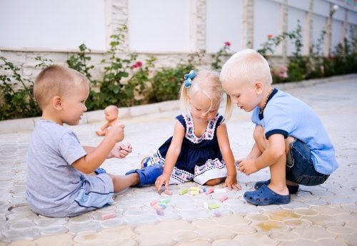 tre barn leker med kritor