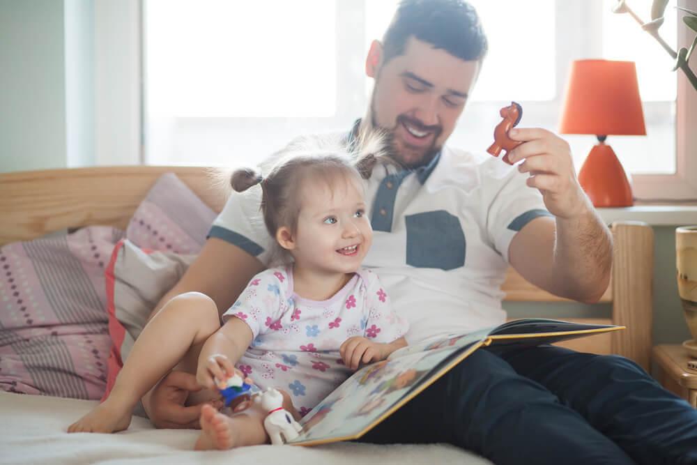 pappa tittar i bok och leker med dotter
