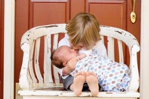 storasyskon håller om nytt litet syskon