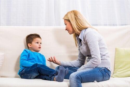 mamma och son pratar på soffa