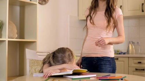 Mamma vid flicka som ligger över sina läxböcker