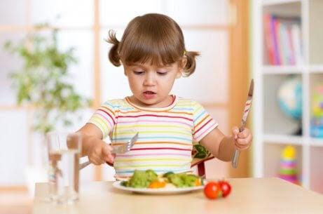 Fint bordsskick: flicka äter sallad