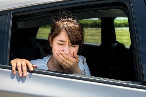 flicka i bil ser illamående ut