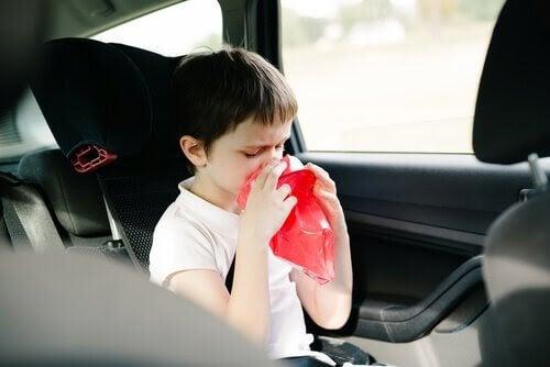 pojke i bil håller kräkpåse framför munnen