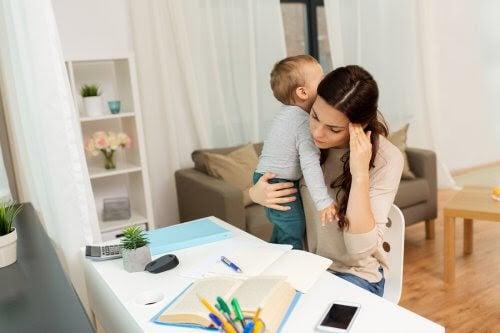 Kvinna försöker plugga med litet barn på armen