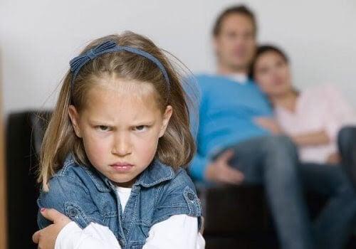 Sur tjej med föräldrar i bakgrunden