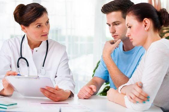 läkare talar med man och kvinna om cervixinsufficiens