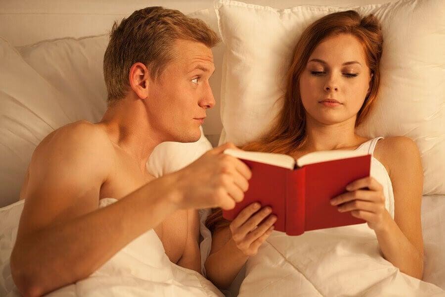 sexualitet och amning: man och kvinna i säng, kvinnan läser och mannen håller en hand på hennes bok