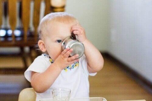 lära sig dricka från en kopp: baby dricker ur kopp