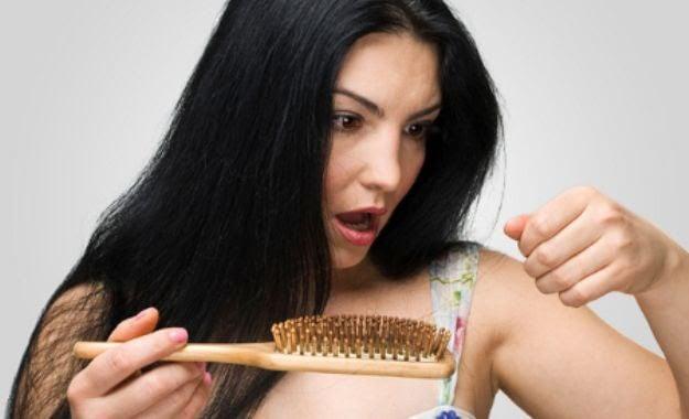 kvinna med hårborste tittar förfärat på tappade hårstrån
