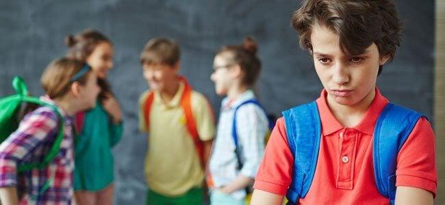 ett barn är utanför när en annan grupp barn pratar