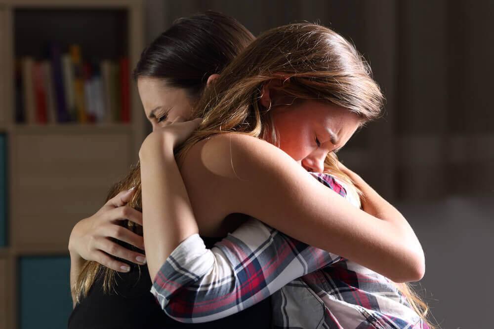 två ledsna unga kvinnor håller om varandra