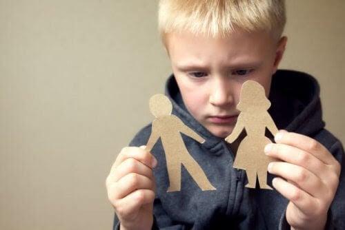 pojke håller upp pappersdockor av kvinna och man