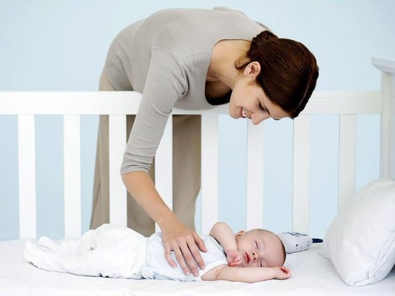 Kvinna klappar bebis i spjälsäng