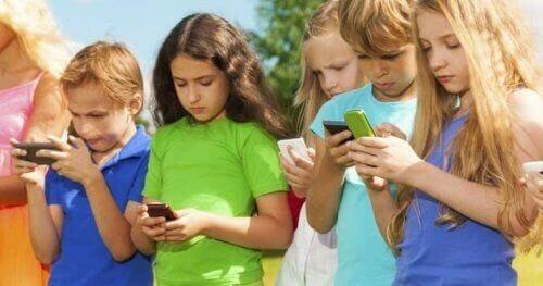 Barn står i rad och tittar på sina smartphones