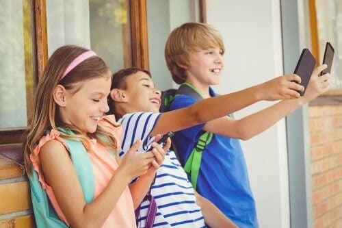 Barn står i rad och tittar på sina smartphones - två tar selfie