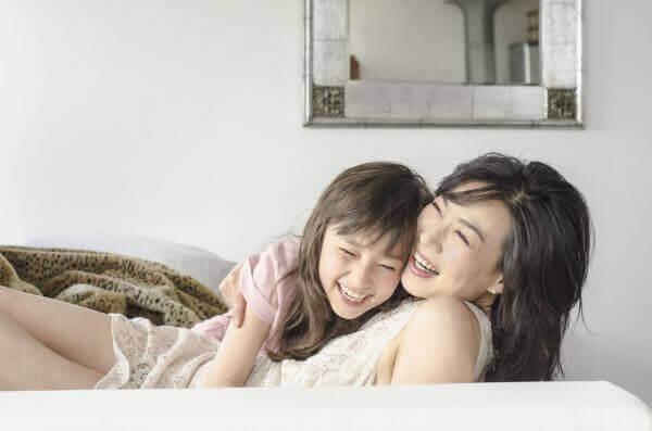 Mamma och dotter leker i säng