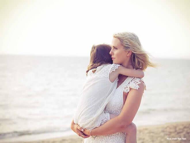 Mamma bär barn på strand