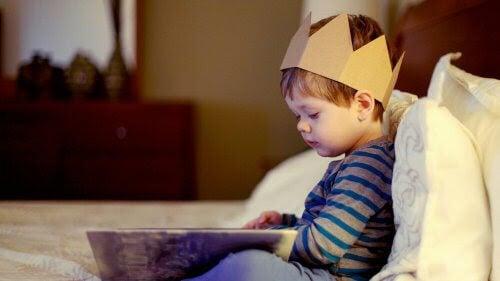 pojke med papperskrona tittar i bok
