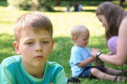 pojke ser svartsjuk ut medan mamma pysslar med baby i bakgrunden
